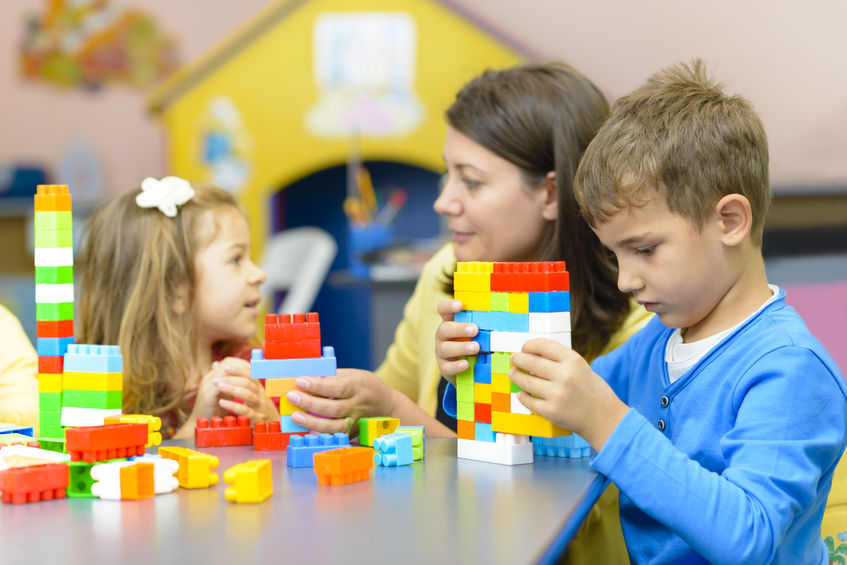 kids playing with plastic building blocks in autism friendly nursery