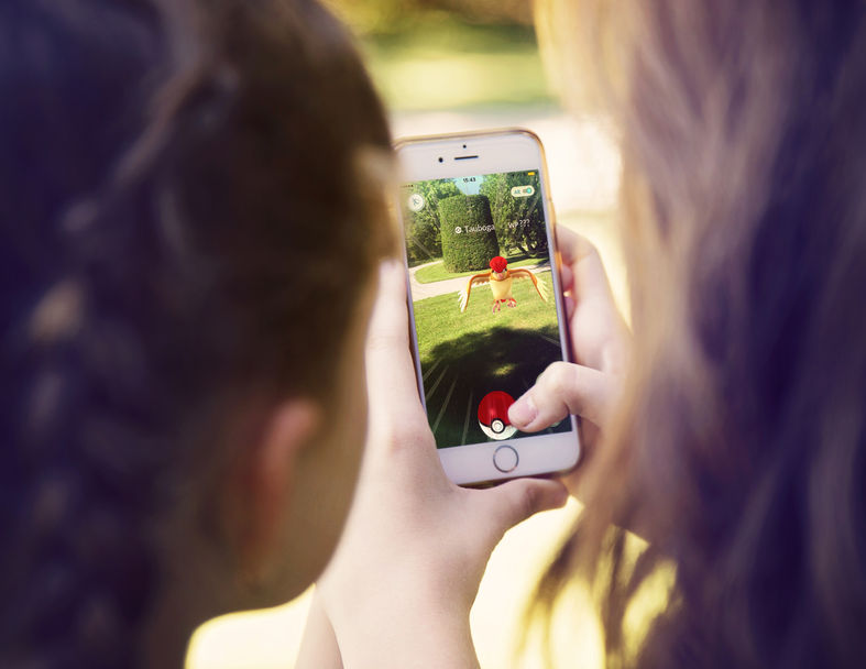 : little girls playing a pokemon go game outdoors. pokemon go is a location-based augmented reality mobile game.