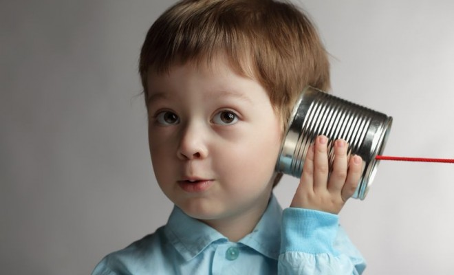 child with tin can phone