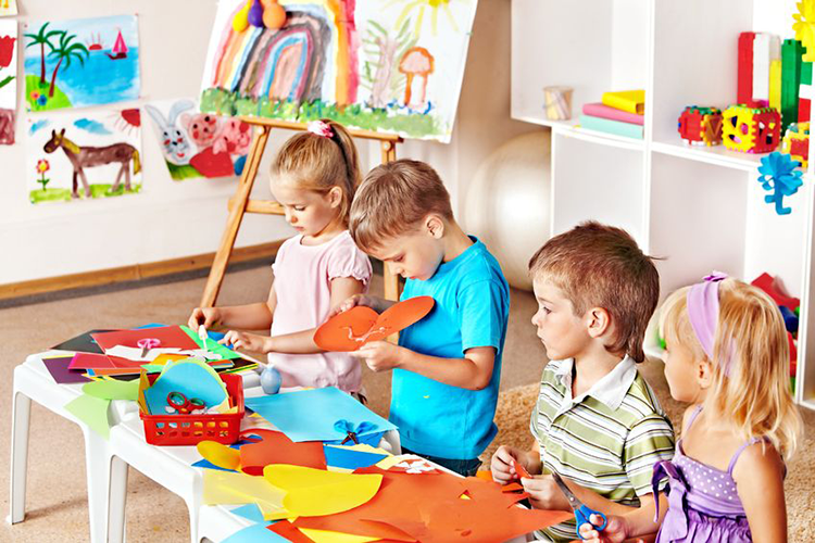 Behavioural difficultiesv- Four children play arts and crafts in nursery