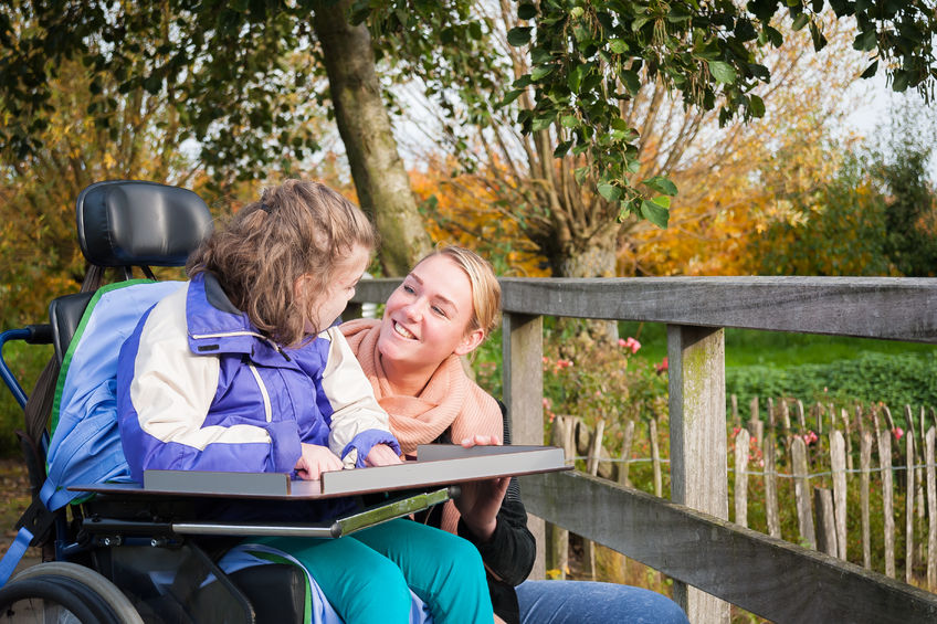 47991012 – disabled child in a wheelchair outside with care assistant