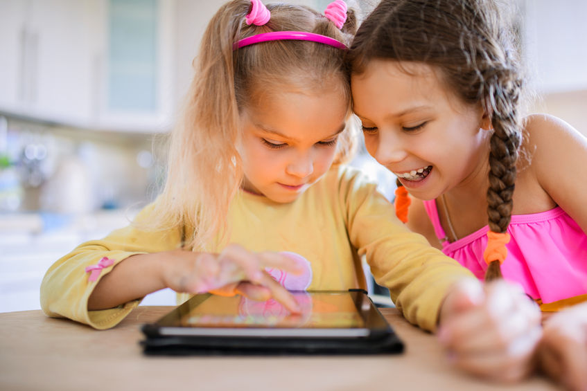 46740750 – two beautiful little sisters sit at a table and play on a tablet pc.