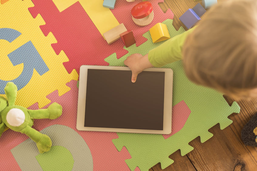 57808332 – top view of a toddler grabbing a tablet device from its playground