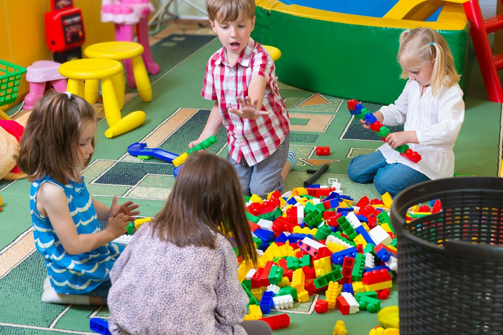 19783570 – group of kids playing with colorful constructor on floor