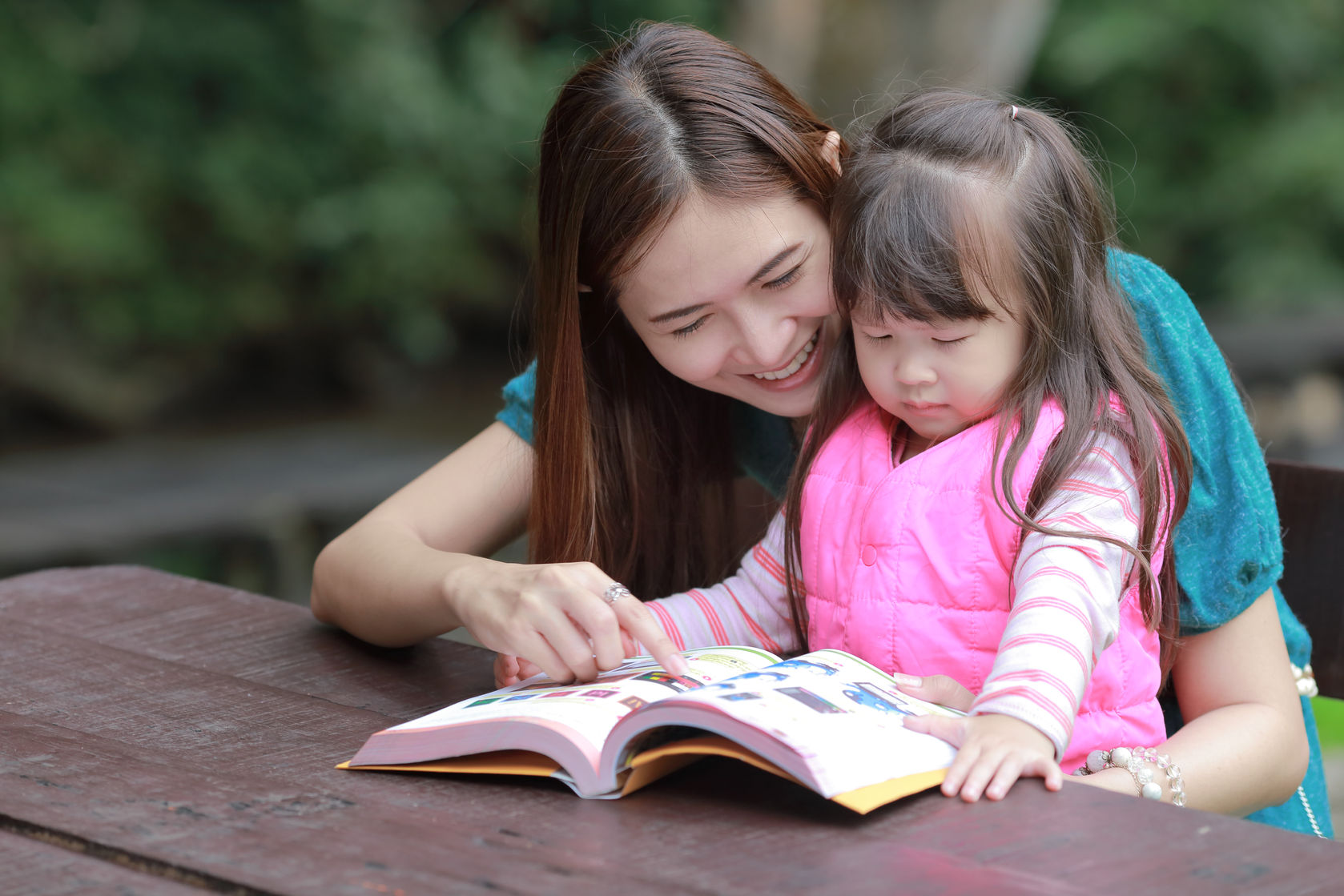 foster parent - lady teaching child to read