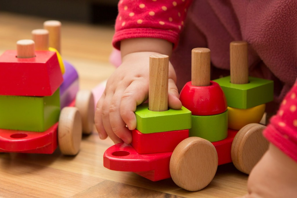 Cognitive Development – baby hand playing with wooden toys