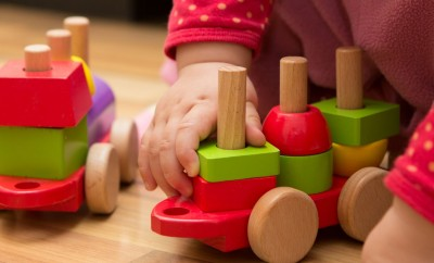 Cognitive Development - baby hand playing with wooden toys