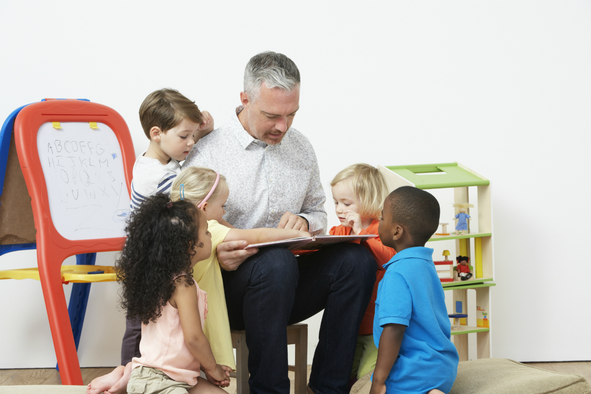 Early years literacy games - teacher reading a story
