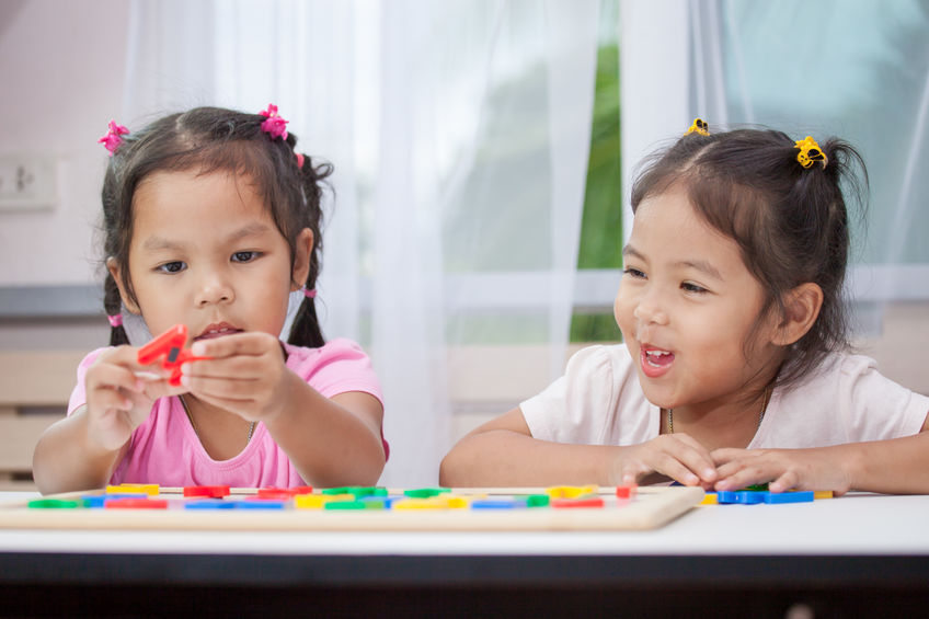 Two cute asian child girls having fun to play and learn magnetic