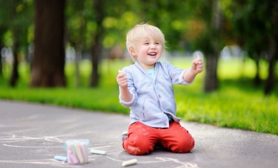 82886777 - happy little kid boy drawing with colored chalk on asphalt. creative leisure for toddler child in summer park. street art, kids education.