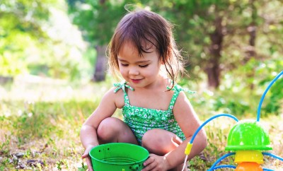 Happy toddler girl playing with water outside